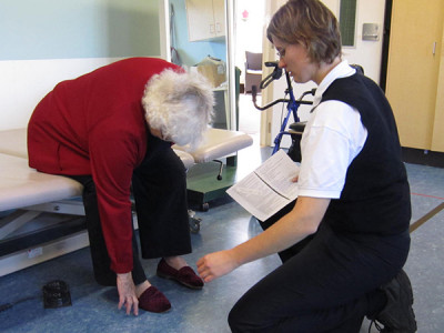 An elderly woman leans down from a hospital bed being assisted with her shoes by a physiotherapist