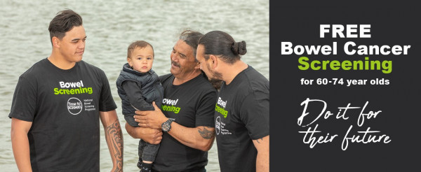A group of Maori males of different ages smiling with a small baby with the river in the background